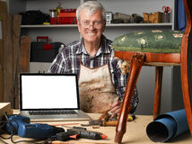Retired carpenter with laptop. Portrait of retired carpenter points out of laptop while sitting in his workshop next to the broken away legged chair. Small Stock Photos