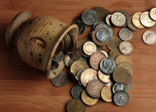 Retired Coins. European coins that for the most part have been replaced by the euro spilling out of a pottery cup Stock Photography