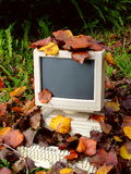 Retired Computer. An old personal computer that has apparently been abandoned outside and become covered with Autumn leaves Royalty Free Stock Image