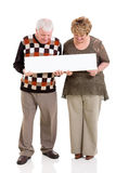 Retired couple banner. Retired couple holding white banner on white background Royalty Free Stock Photos
