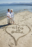 Retired Couple on Beach. Happy retired couple on beach writing with stick in the sand Stock Photography