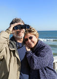 Retired couple on beach vacation with binoculars hugging Stock Photo