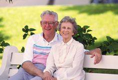 Retired Couple on Bench. Retired couple sitting together on a park bench, happy on a beautiful sunny day Royalty Free Stock Photos