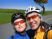 Retired Couple Biking. Active retired couple having fun on a bike trip Royalty Free Stock Image