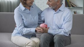 Retired couple on couch holding piggy bank, matured paid out insurance, secure. Stock footage stock video footage