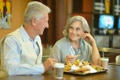 Retired couple eating french fries Stock Photos