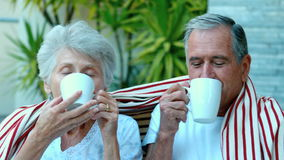 Retired couple enjoying coffee outside