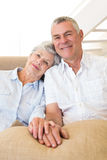 Retired couple holding hands on couch smiling at camera Stock Photography