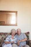 Retired couple at home using digital tablet. Vertical indoor shot of retired couple at home using digital tablet. Senior caucasian men and women sitting together Royalty Free Stock Image