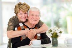 Retired couple hugging. Lovely retired elderly couple hugging at home Stock Images