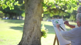Retired couple painting a tree together on canvas Royalty Free Stock Image