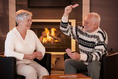 Retired couple playing cards in front of fireplace Royalty Free Stock Photos