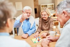 Retired couple plays with friends board game. Seniors as retired couple plays with friends a board game in retirement home or at home royalty free stock photography