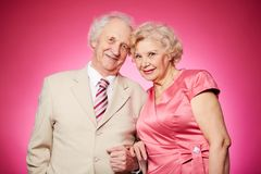 Retired couple. Portrait of a charming retired couple posing against pink background Stock Image