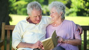 Retired couple reading a book together. While sitting on a park bench stock video