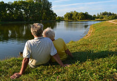 Retired couple relaxing. Retired couple sitting and relaxing on a lakeside Royalty Free Stock Photos