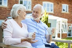 Retired Couple Sitting On Bench With Hot Drink In Assisted Living Facility royalty free stock image