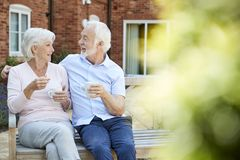 Retired Couple Sitting On Bench With Hot Drink In Assisted Living Facility stock photos