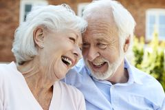 Retired Couple Sitting On Bench And Talking In Assisted Living Facility stock photo