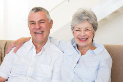 Retired couple sitting on couch smiling at camera Stock Photos