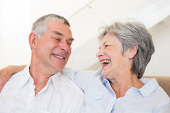 Retired couple sitting on couch smiling at each other Royalty Free Stock Image