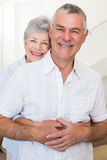 Retired couple smiling at camera and hugging Royalty Free Stock Image