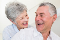 Retired couple smiling at each other and hugging Stock Image