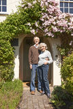 Retired Couple Standing Outside Pretty Cottage Royalty Free Stock Image
