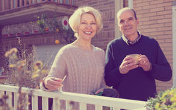 Retired couple on a terrace. Retired couple outside their house on a terrace with gardening instruments and a cup of hot beverage stock photo