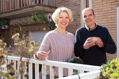 Retired couple on a terrace. Retired couple outside their house on a terrace with gardening instruments and a cup of hot beverage royalty free stock image