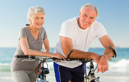 Retired couple with their bikes on the beach royalty free stock photos