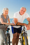 Retired couple with their bikes on the beach. Active retired couple with their bikes on the beach Royalty Free Stock Photo