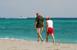 Retired couple walking on beach Royalty Free Stock Photos