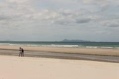 Retired couple walking on Pakiri Beach Royalty Free Stock Photos
