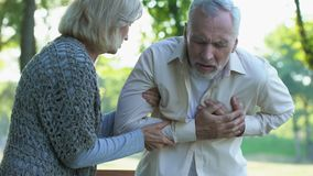Retired couple walking in park, male pensioner suffering from heart attack