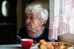 Retired elderly lone woman in the kitchen of his house sitting at the table stock image