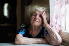 Retired elderly woman in the kitchen of his house . royalty free stock photography