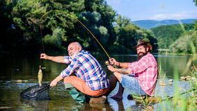 Retired father and mature bearded son. big game fishing. relax on nature. fly fish hobby of men. retirement fishery