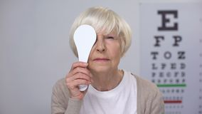 Retired female closing eye and smiling to camera, successful cataract surgery. Stock footage stock video footage