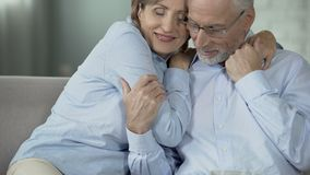 Retired female hugging husband who is reading newspaper, happy elderly couple stock video footage