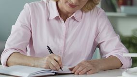 Retired female thinking about start-up plan and writing ideas down in notebook. Stock footage stock video