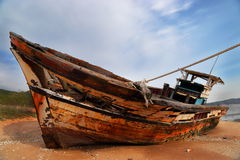 Retired fishing boat. A deteriorating retired fishing boat on a beach sand Stock Photos