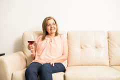 Retired granny doing a toast by herself Royalty Free Stock Image