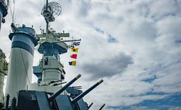 Retired Warship. A retired, hulking warship`s nautical flags blow majestically in the wind Stock Photos
