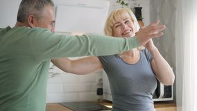 Retired husband and female pensioner dancing in kitchen during salad preparing. stock video