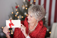 Retired lady with a christmas gift voucher. Glamorous retired lady with a christmas gift voucher displaying the blank white envelope with a red ribbon in front Stock Photos