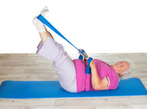 Retired lady doing exercises. Lying on a gym mat raising her legs in the air to strengthen her abdominal muscles Royalty Free Stock Photography
