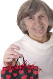 Retired lady holding gift bag Royalty Free Stock Photos
