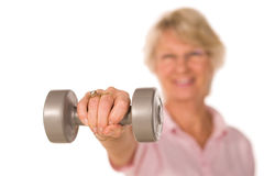 Retired lady lifting weights. Mature retired lady lifting weights during gym workout Royalty Free Stock Photography