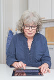 Retired lady with tablet-pc. Retired lady with glasses typing on her tablet-pc Stock Photography